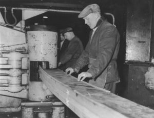 Shipyard workers at a cold frame bending machine